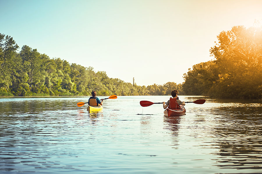 About Our Agency - Two Men Kayaking on a River
