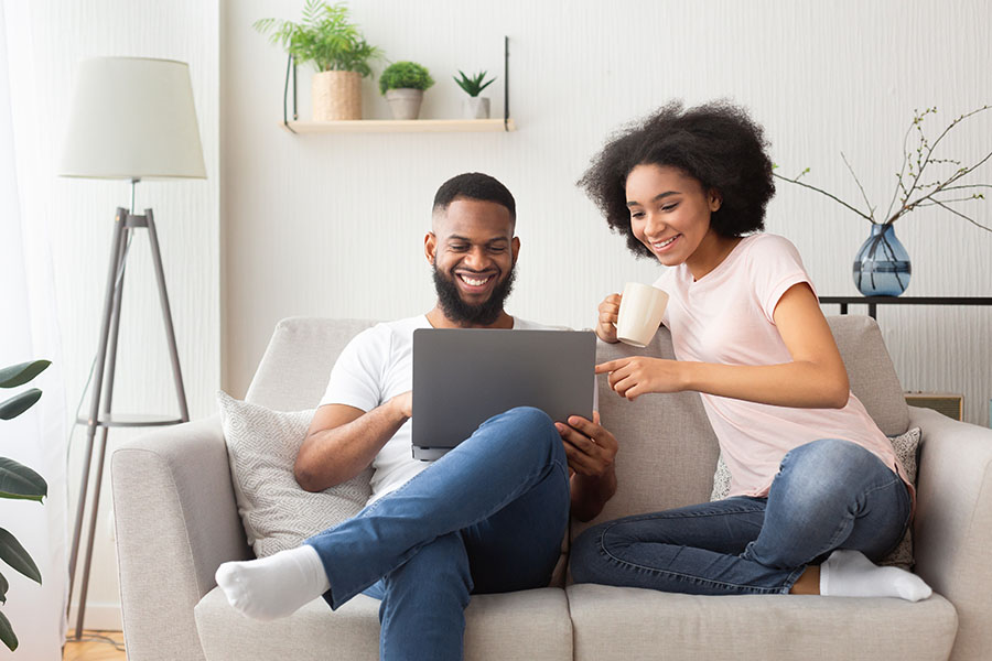 Blog - Couple Sharing Laptop and Coffee on Their Couch