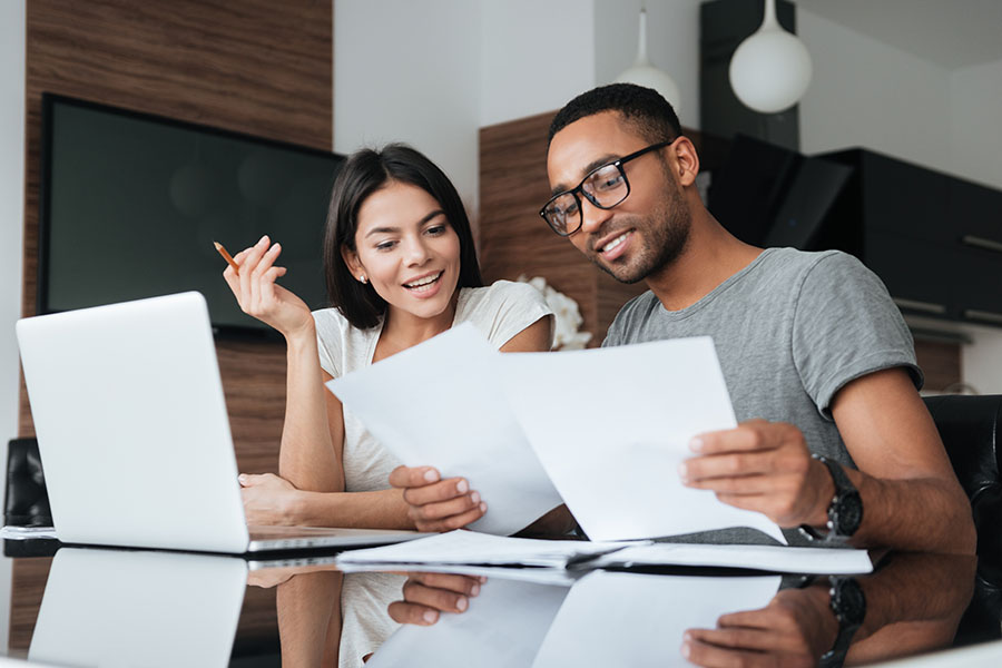 Client Center - Young Couple Reviewing Paperwork and Using Laptop Together