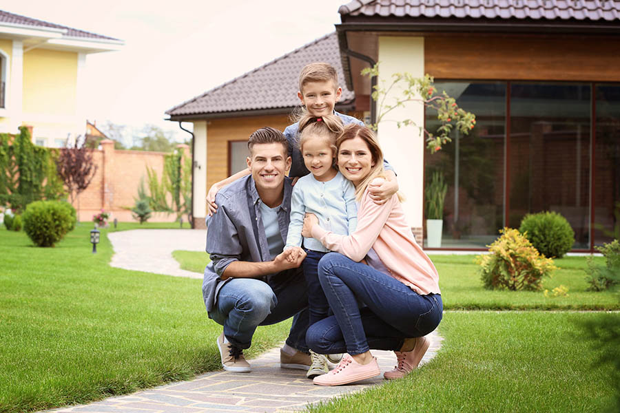Personal Insurance - Young Mother, Father, Son and Daughter Crouch Together Smiling Outside of a Large Home With a Manicured Lawn and Paved Walkway