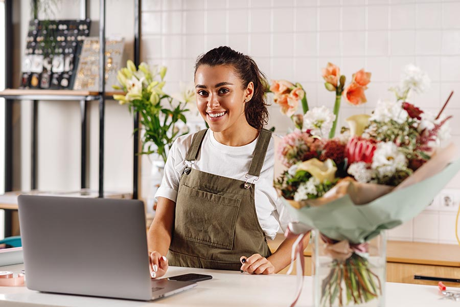 Business Insurance - Flower Shop Owner in Green Overalls Smiles Behind White Counter Using a Laptop, Surrounded by Floral Arrangements and Tools